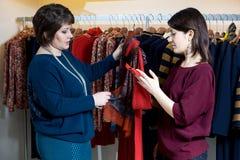 Deux femmes heureuses faisant des emplettes dans le magasin de vêtements Photos libres de droits