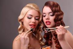 Deux femmes heureuses mangeant des petits pains de sushi Photographie stock libre de droits