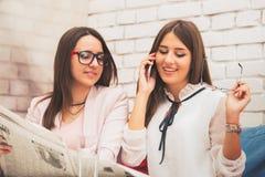 Deux femmes heureuses recherchent un travail dans le journal photo libre de droits