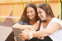 Deux femmes heureuses regardant dans le PC de comprimé dans la rue Image libre de droits