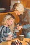Deux femmes heureuses s'asseyant dans un café, boivent d'un thé chaud, se racontent des histoires drôles, étant dans une bonne hu photo stock
