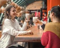 Deux femmes heureuses s'asseyent dans un café, buvant des milkshakes photo libre de droits
