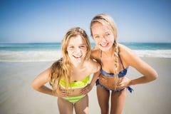 Deux femmes heureuses se tenant sur la plage avec la main sur la hanche Photographie stock libre de droits