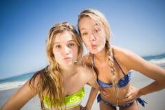 Deux femmes heureuses se tenant sur la plage avec la main sur la hanche Photos libres de droits