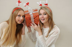 Deux femmes heureuses se tiennent près de la tête et écoutent boîte-cadeau Photographie stock