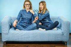 Deux femmes heureuses tenant de fausses lunettes sur le bâton Images libres de droits