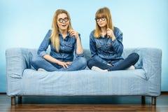 Deux femmes heureuses tenant de fausses lunettes sur le bâton Photographie stock libre de droits