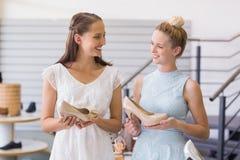 Deux femmes heureuses tenant des chaussures de talon Image stock
