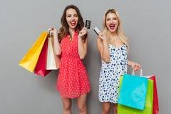 Deux femmes heureuses tenant des paniers et des cartes de crédit Images libres de droits