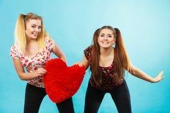 Deux femmes heureuses tenant l'oreiller en forme de coeur Photo stock