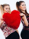 Deux femmes heureuses tenant l'oreiller en forme de coeur photo libre de droits