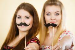 Deux femmes heureuses tenant la fausse moustache sur le bâton Images libres de droits