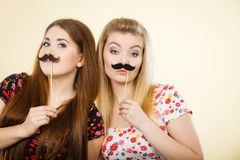 Deux femmes heureuses tenant la fausse moustache sur le bâton images stock