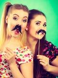 Deux femmes heureuses tenant la fausse moustache sur le bâton Photos stock