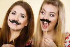 Deux femmes heureuses tenant la fausse moustache sur le bâton Photos libres de droits