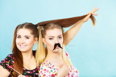 Deux femmes heureuses tenant la fausse moustache sur le bâton Photo libre de droits
