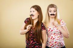 Deux femmes heureuses tenant la fausse moustache sur le bâton Photographie stock