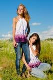 Deux femmes heureux ayant l'amusement, posant et appréciant le soleil Photographie stock