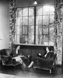 Deux femmes jouant des cartes et s'asseyant ensemble (toutes les personnes représentées ne sont pas plus long vivantes et aucun d Photo libre de droits