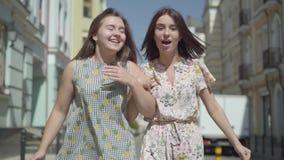 Deux femmes joyeuses avec des sacs à provisions marchant par la rue de ville Jeunes filles portant apprécier élégant de robes d'é banque de vidéos