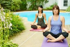 Deux femmes mûres maintenant l'ajustement en faisant le yoga pendant l'été Photo stock