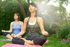 Deux femmes mûres maintenant l'ajustement en faisant le yoga pendant l'été Image stock