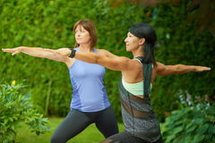Deux femmes mûres maintenant l'ajustement en faisant le yoga pendant l'été Photographie stock libre de droits