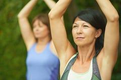 Deux femmes mûres maintenant l'ajustement en faisant le yoga pendant l'été Images stock