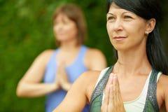 Deux femmes mûres maintenant l'ajustement en faisant le yoga pendant l'été Image libre de droits