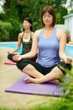 Deux femmes mûres maintenant l'ajustement en faisant le yoga pendant l'été Photo libre de droits