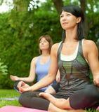 Deux femmes mûres maintenant l'ajustement en faisant le yoga pendant l'été Images libres de droits