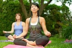 Deux femmes mûres maintenant l'ajustement en faisant le yoga pendant l'été Photos libres de droits
