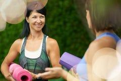Deux femmes mûres parlant avant de faire le yoga pendant l'été Image libre de droits
