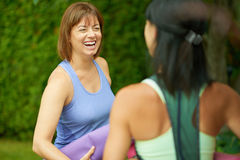 Deux femmes mûres parlant avant de faire le yoga pendant l'été Photo libre de droits