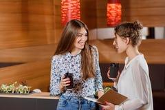 Deux femmes magnifiques causant et tenant les tasses de papier avec du café photo stock