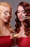 Deux femmes mangeant des petits pains de sushi Image stock