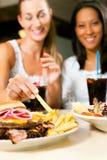 Deux femmes mangeant l'hamburger et buvant le bicarbonate de soude Image stock