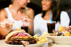 Deux femmes mangeant l'hamburger et buvant le bicarbonate de soude Photo libre de droits