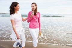 Deux femmes marchant le long de la plage regardant le téléphone portable Photographie stock libre de droits