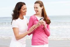 Deux femmes marchant le long de la plage regardant le téléphone portable Image stock