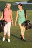 Deux femmes marchant le long du terrain de golf Images libres de droits