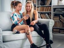 Deux femmes modernes détendant sur un divan et à l'aide du smartphone dans un l Photographie stock libre de droits