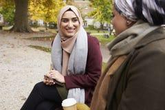 Deux femmes musulmanes britanniques mangeant le déjeuner en parc ensemble Photo stock