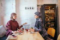 Deux femmes musulmanes en café, se réunir d'amis Image libre de droits