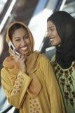 Deux femmes musulmanes une utilisant le téléphone portable Images stock