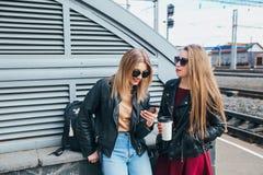 Deux femmes parlant dans la ville Portrait extérieur de mode de vie de deux filles de hippie de meilleurs amis portant le cuir él Photo stock
