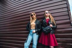 Deux femmes parlant dans la ville Portrait extérieur de mode de vie de deux filles de hippie de meilleurs amis portant le cuir él Image stock