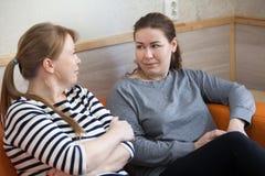 Deux femmes parlant ensemble tout en reposant le sofa d'intérieur Photo libre de droits