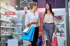 Deux femmes parlant et riant après l'achat dans le magasin de cosmétiques photo libre de droits
