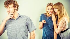 Deux femmes parlant le bavardage au sujet de l'homme Photo stock